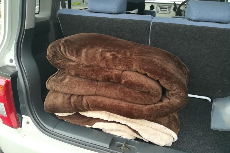 写真:こたつ布団をコインランドリーで洗濯するため、車に載せる