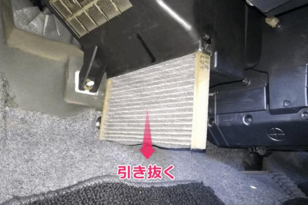 写真:古いエアコンフィルターを引き抜く